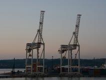 Kranar och behållare i skeppsvarv på skymning Royaltyfri Fotografi