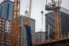 Kranar och byggande apparat på en konstruktionsplats av en skyskrapa i dowtown Montreal som omges av andra höga löneförhöjningtor arkivbild