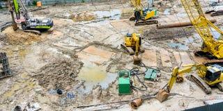 Kranar och grävskopor i konstruktionsplats royaltyfri bild