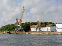 Kranar och industribyggnader i den Liepaja hamnen Royaltyfria Foton
