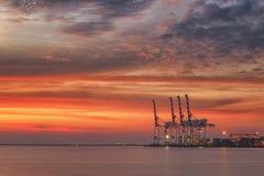 Kranar och industriella lastfartyg i Varna port på solnedgången Royaltyfri Fotografi