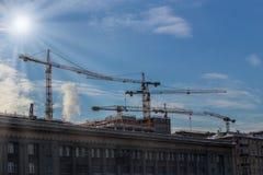 Kranar på konstruktionsplatsen av moderna byggnader Arkivbild