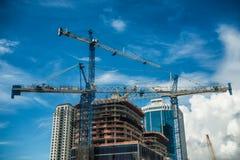 Kranen bij de moderne wolkenkrabberbouw in stad bij zonnige dag met blauwe hemel stock afbeelding