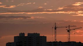 Kranen en gebouwen, zonsondergangachtergrond stock video