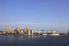 Kranen en graanschuuren, reservoirs met tarwe in de haven in duidelijk weer, het overzees royalty-vrije stock afbeelding