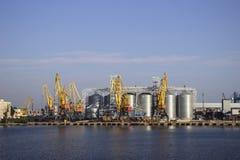 Kranen en graanschuuren, reservoirs met tarwe in de haven in duidelijk weer, het overzees royalty-vrije stock foto's