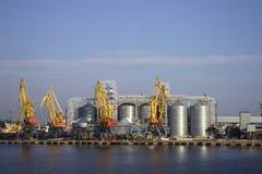 Kranen en graanschuuren, reservoirs met tarwe in de haven in duidelijk weer, het overzees stock foto's