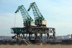 Kranen en scrapyard Stock Foto's