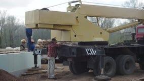 Kranen för konstruktionsplatsen lyfter för byggande hus gem Kran för byggande av ett hus lager videofilmer