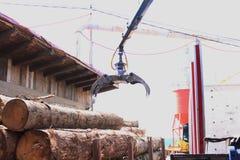 Kranen flyttar trät från lastbilen till sågen arkivfoton