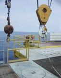 Kranen hissar, låser huvudsakliga och hjälpkrokar med säkerhet och vägleda remmen på den avlägsna frånlands- oljaproduktionplattf arkivbilder
