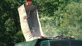 Kranen lastar av brutna tegelstenar till en lastbil stock video
