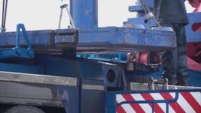 Kranen lyfter den tunga järndetaljen gem För metalllastningsbrygga för industriellt järn stor kran med en krok som monteras på se stock video