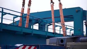 Kranen lyfter den tunga järndetaljen gem För metalllastningsbrygga för industriellt järn stor kran med en krok som monteras på se lager videofilmer
