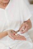 Kranke ältere Frau, die ihre Pillen nimmt stockfotografie
