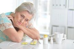 Kranke ältere Frau mit Medikation stockbild