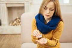 Kranke blonde Frau, die Pillen einnimmt Lizenzfreie Stockbilder