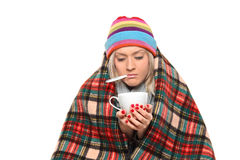 Kranke Frau deckte mit der Decke ab, die ein Teecup anhält Lizenzfreies Stockbild