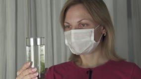Kranke Frau in der medizinischen Maske löst die schäumende Tablette in einem Glas Wasserzeitlupevorrat-Gesamtlängenvideo auf stock video footage