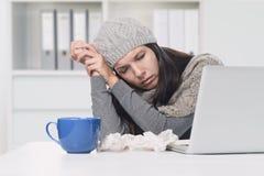Kranke Frau in der Winter-Kleidung mit Laptop und Tee Lizenzfreies Stockbild