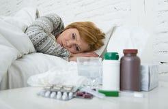Kranke Frau, die das schlechte kranke Lügen auf Kopfschmerzenwinterkälte- und -grippevirus des Betts dem leidenden hat Medizin si Lizenzfreies Stockfoto