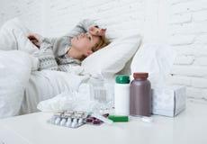 Kranke Frau, die das schlechte kranke Lügen auf Kopfschmerzenwinterkälte- und -grippevirus des Betts dem leidenden hat Medizin si Lizenzfreie Stockfotos