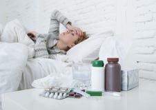 Kranke Frau, die das schlechte kranke Lügen auf Kopfschmerzenwinterkälte- und -grippevirus des Betts dem leidenden hat Medizin si Lizenzfreie Stockbilder