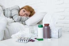 Kranke Frau, die das schlechte kranke Lügen auf Kopfschmerzenwinterkälte- und -grippevirus des Betts dem leidenden hat Medizin si Stockfoto