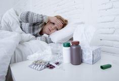 Kranke Frau, die das schlechte kranke Lügen auf Kopfschmerzenwinterkälte- und -grippevirus des Betts dem leidenden hat Medizin si Stockfotos