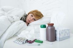Kranke Frau, die das schlechte kranke Lügen auf Kopfschmerzenwinterkälte- und -grippevirus des Betts dem leidenden hat Medizin si Stockfotografie