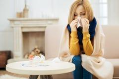 Kranke Frau, die ihre Nase durchbrennt stockfotografie