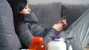 Kranke Frau, die Smartphone beim auf der Couch zu Hause liegen verwendet stock video