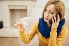 Kranke Frau, die Temperatur nimmt und telefonisch spricht stockfotografie