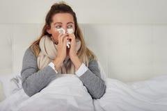 Kranke Frau mit dem Saisonkälte- und Grippelügen oben warm eingewickelt im Bett stockfotos