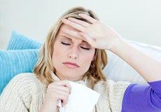 Kranke Frau mit den Kopfschmerzen, die zu Hause auf dem Sofa liegen Lizenzfreies Stockbild