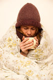 Kranke Frau mit feaver Trinkbecher warmem Tee unter Decke Lizenzfreie Stockfotos