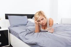 Kranke Frau mit Satz Pillen, die auf Bett liegen Lizenzfreies Stockbild
