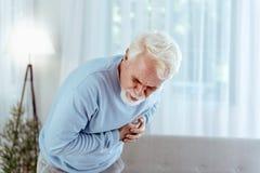 Kranke Gefühlsschmerz des älteren Mannes im Kasten lizenzfreies stockbild