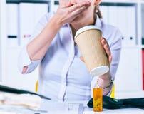 Kranke Geschäftsfrau, die medizinische Pillen am Arbeitsplatz, leiden unter den Migränekopfschmerzen hält und fühlen sich schlech Lizenzfreies Stockfoto