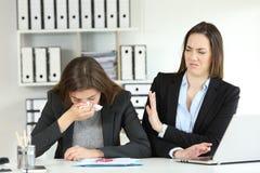 Kranke Geschäftsfrau und ein Kollege, der sie zurückweist lizenzfreie stockfotos