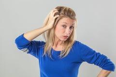 Kranke junge blonde Frau mit den Taschen, die ihr Haar verkratzen Lizenzfreie Stockfotos