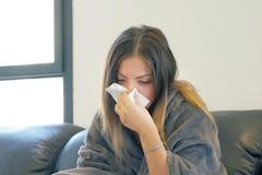 Kranke junge Frau, die auf einer schwarzen Couch sitzt und seine Nase in eine Serviette durchbrennt stockfoto