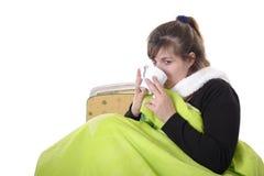 Kranke junge Frau, die unter einer Bettdecke sitzt lizenzfreies stockfoto