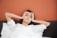 Kranke junge Frauen auf Bett mit Kopfschmerzen stockbild