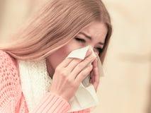 Kranke kranke Frau im Herbstpark niesend im Gewebe lizenzfreie stockfotografie