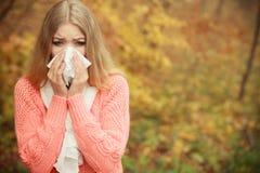 Kranke kranke Frau im Herbstpark niesend im Gewebe stockbilder