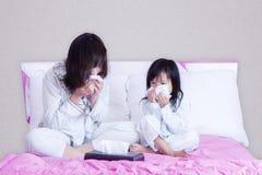 Kranke Mutter und Kind, die Nase abwischt Stockfotos