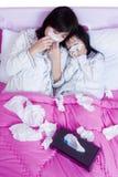 Kranke Mutter und Tochter, die auf Bett liegt Stockbild