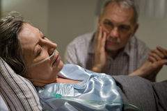 Kranke reife Frau, die im Bett liegt Lizenzfreie Stockfotos