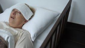 Kranke reife Frau, die im Krankenhausbett mit Kompresse auf Stirn, Fieber oder Grippe liegt stock video